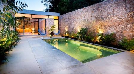 piscina con solarium con pared de piedras